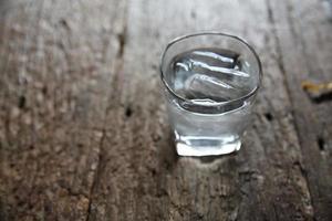 água em vidro no fundo madeira foto