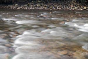 água corrente em um pequeno riacho foto