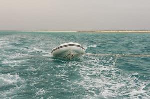 pequeno barco sendo rebocado em um mar tropical