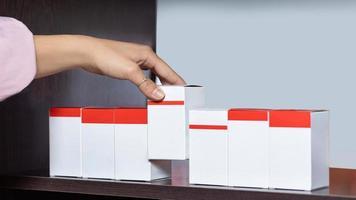 mulher pegando uma caixa branca em branco de uma prateleira