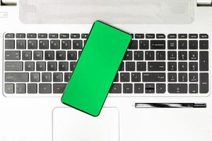 tela verde do smartphone no teclado do laptop