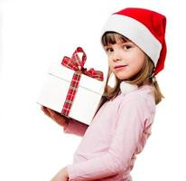 criança com chapéu de Papai Noel segurando um presente de natal
