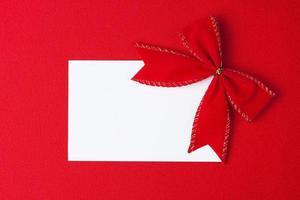 cartão em branco com laço sobre fundo vermelho foto