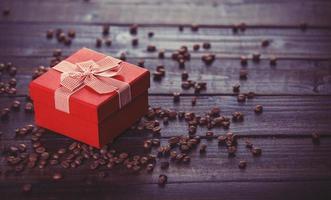 caixa de presente vermelha e café na mesa de madeira.