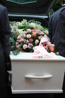 caixão branco em um carro funerário cinza
