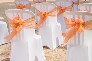 cadeiras brancas com laços laranja.