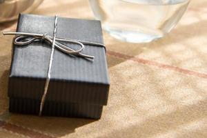 pequena caixa de presente com um laço prateado ao sol da manhã