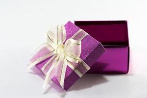caixa de presente roxa com fita dourada e laço