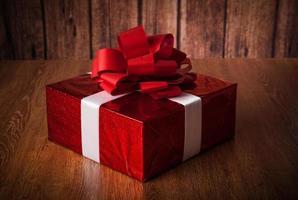 uma grande caixa de presente vermelha em uma madeira