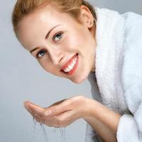 jovem lavando o rosto foto