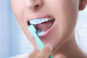 mulher com escova de dente