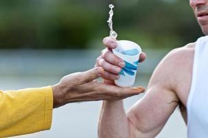 uma maratona correndo segurando um copo de água foto
