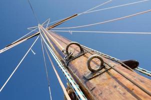 mastro de madeira antigo com travessas e backstays, vista do convés