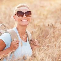 garota viajante feliz no campo de trigo