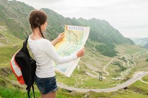 turista de garota na montanha ler o mapa.