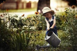 menino com regador no parque de verão foto