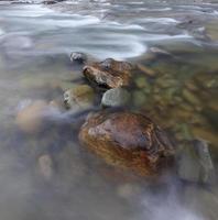 foto de longa exposição de um rio com pedras