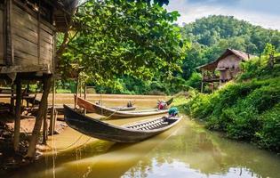 barcos de cauda longa atracados em uma vila, na Tailândia foto