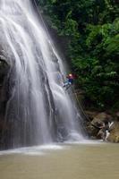 homem descendo de rapel de um penhasco de cachoeira foto