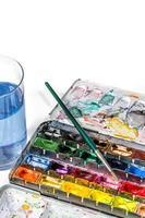 caixa de tinta aquarela com pincel e copo d'água
