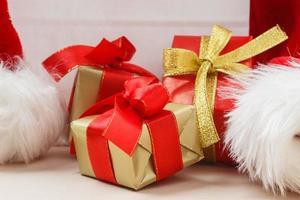 pequenas caixas vermelhas e douradas com presentes amarrados com laços