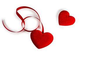 dois corações com fita vermelha isolada no branco foto