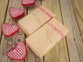 pacotes de papel marrom e barbante com fita xadrez vermelha