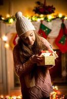 garota vestindo suéter olhando para uma caixa de presente na véspera de natal