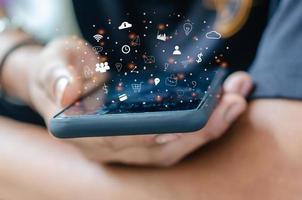 mão segurando smartphone com ícones