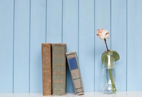 pilha de livros e rosa branca na garrafa foto