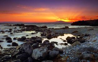 glorioso pôr do sol sobre o mar rochoso foto