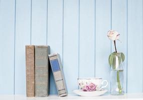 livros antigos, xícara de porcelana e rosa na estante foto