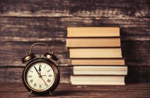 despertador e livros na mesa de madeira. foto