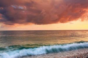 nascer do sol tempestuoso na costa do mar foto