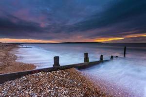 groynes ao pôr do sol em Milford-on-Sea