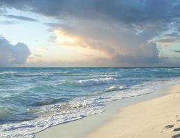 Nuvens de tempestade matinal sobre a praia no mar do Caribe