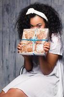 bela jovem feliz segurando um presente de natal, biscoitos