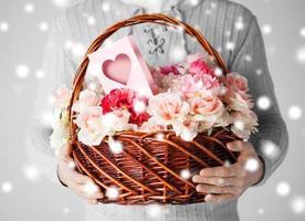 homem segurando uma cesta cheia de flores e cartão postal