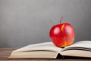 maçã vermelha e livro sobre uma mesa.