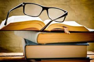 livro aberto com óculos de leitura foto