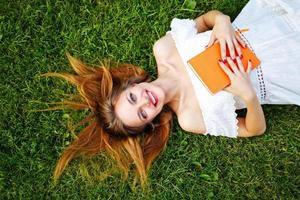 menina com o livro deitado no gramado. foto