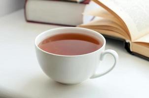 xícara de chá preto e alguns livros sobre a mesa