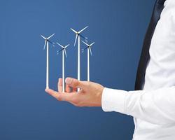 mãos segurando turbina eólica