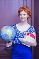 garota segurando um globo mundial e livros foto