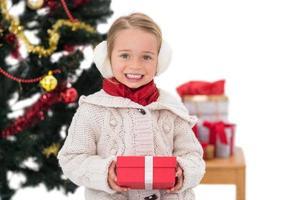 menina festiva segurando um presente foto