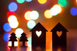 duas casas com buraco em forma de coração com árvores de natal