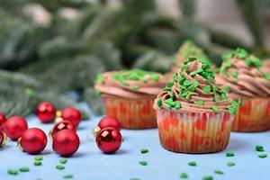cupcakes com creme de chocolate em um fundo azul de madeira foto
