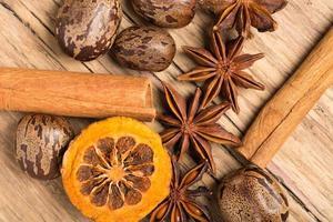 decoração de natal em fundo de madeira com canela, laranja, nozes