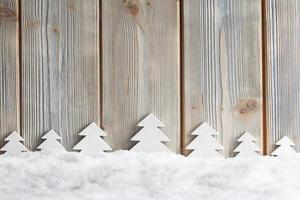 árvores de natal na neve e fundo de madeira