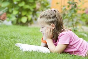 menina lendo um livro no parque